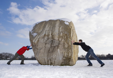 2 men pushing boulder