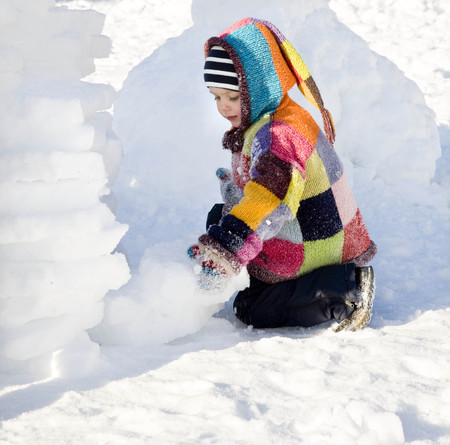 agachado: niño construyendo iglú en la nieve
