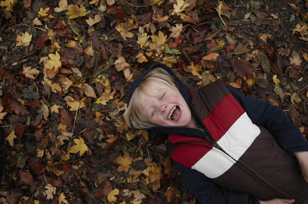 mischievious: Young boy lying on autumn leaves