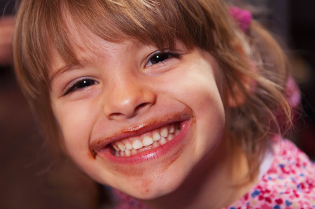 enthusiastically: Girl smiling with chocolate around mouth