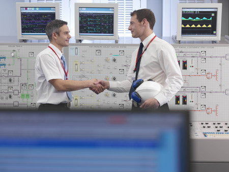 english ethnicity: Operators shaking hands in control room