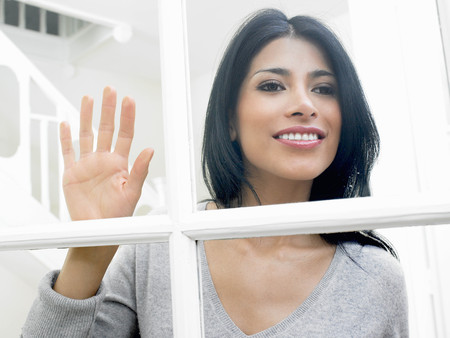 enthusiastically: Woman looking through window