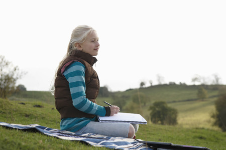 Young girl sketching on hillside