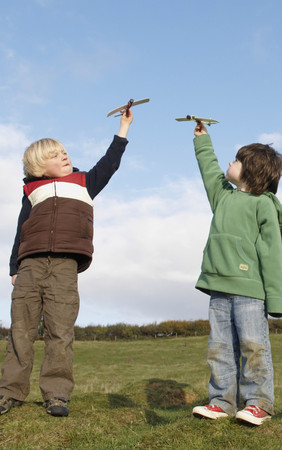 in twos: Boys with toy planes in field LANG_EVOIMAGES