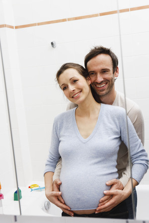 regard: Pregnant woman and man looking in mirror