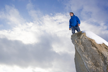 man standing on snow covered peak