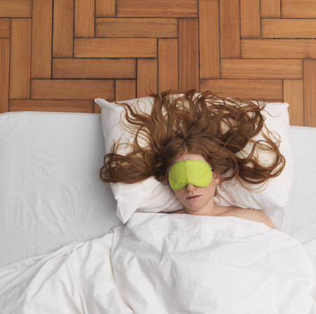 Woman sleeping, wearing eye-mask LANG_EVOIMAGES