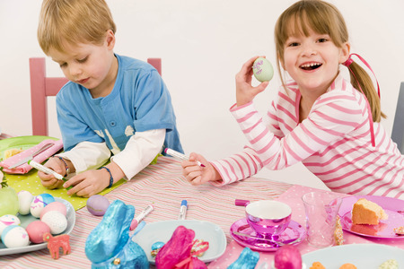 rejoices: girl and boy painting eggs for easter