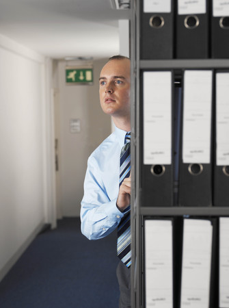 adverse: Office worker hiding behind files