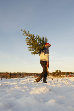 Man with Christmas tree in snow LANG_EVOIMAGES