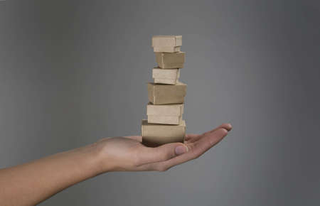 appendage: Female hands holding pile of small boxes