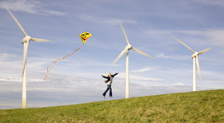 Man jumping with kite at Wind Turbines LANG_EVOIMAGES