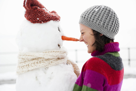 woman nose to nose with snowman