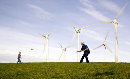 Man,  boy play Frisbee at Wind Turbines