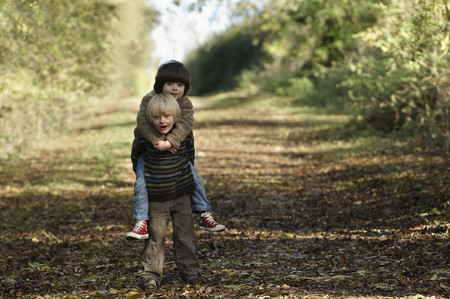 obligations: Young boy carrying friend in countryside LANG_EVOIMAGES