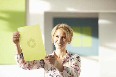 environmentalism: Woman looking at green sheet with logo