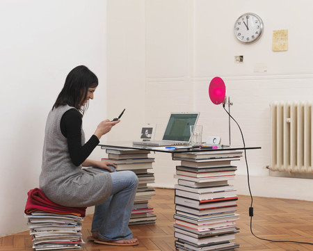 teleworking: Woman sitting at desk, holding phone LANG_EVOIMAGES