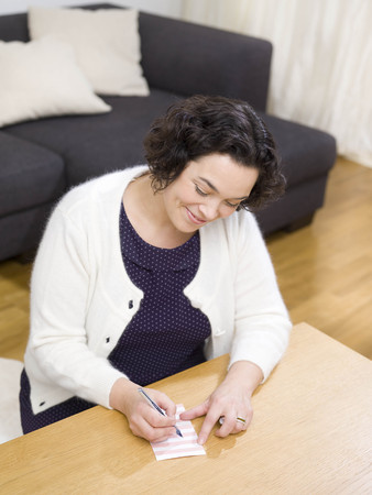 Woman writing a list. LANG_EVOIMAGES