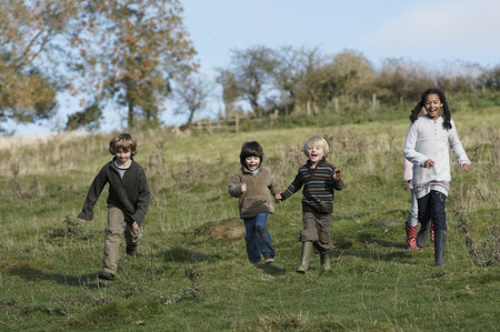enthusiastically: Children running down hill in field LANG_EVOIMAGES