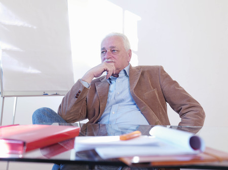 musing: Senior executive sitting at desk LANG_EVOIMAGES