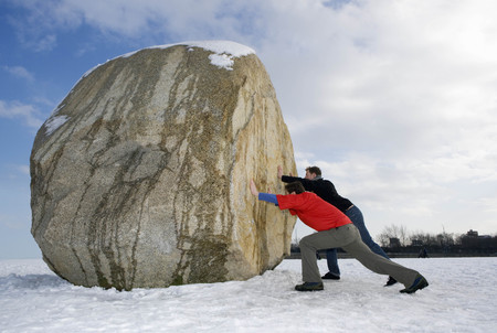 2 men pushing massive boulder