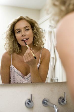 pyjama: Woman putting on make up LANG_EVOIMAGES