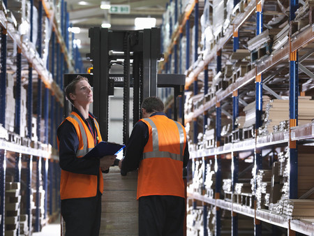 toils: Workers And Forklift In Warehouse