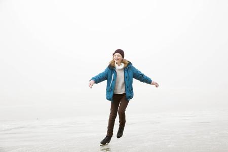 exhilarating: Girl iceskating on frozen lake