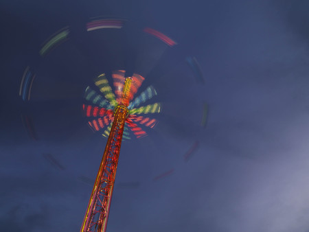 peril: Illuminated chairoplane against dark sky LANG_EVOIMAGES