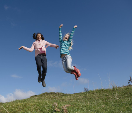 shrieking: Two young girls jumping on hill LANG_EVOIMAGES