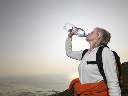 woman hiking drinking water