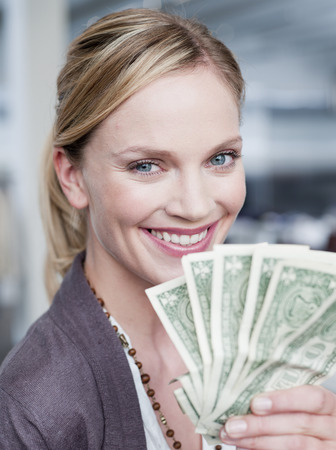 remuneración: woman holding up dollar bills