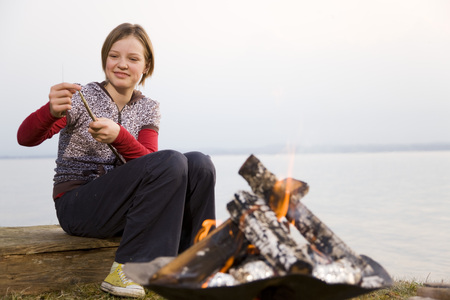 girl carving stick at barbecue fire LANG_EVOIMAGES