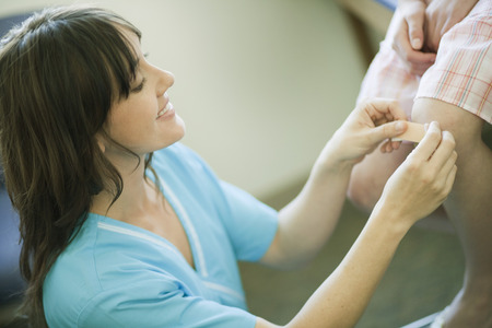 caregivers: Nurse putting plasterbandage on knee LANG_EVOIMAGES