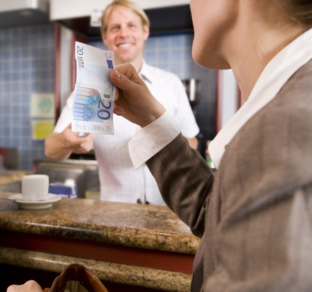 businesswoman paying barkeeper in bar LANG_EVOIMAGES