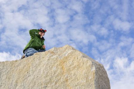 rockclimber: Climber looking through binoculars