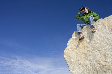Climber looking through binoculars