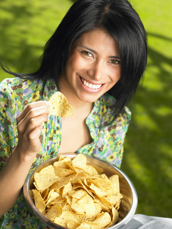 snacking: Woman eating chips, outdoors LANG_EVOIMAGES