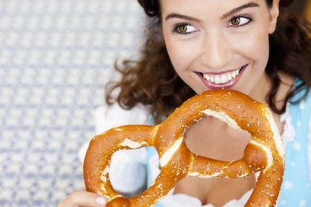 Young Woman Eating Huge Pretzel