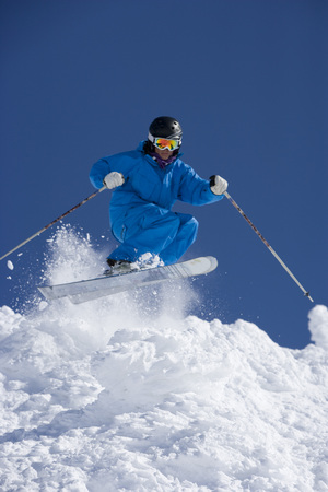 Man in blue jump-suit skiing.