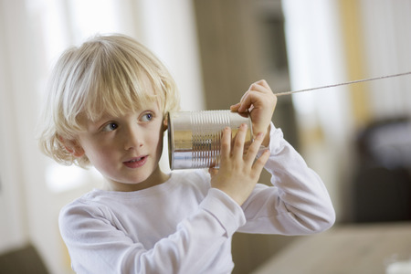 niños platicando: young boy playing with can phone