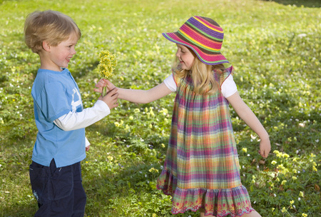girl giving spring flower bouquet to boy