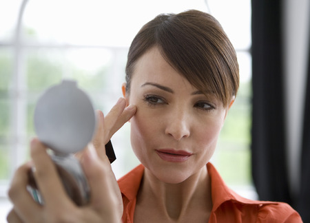 matures: Woman looking at skin in a mirror.