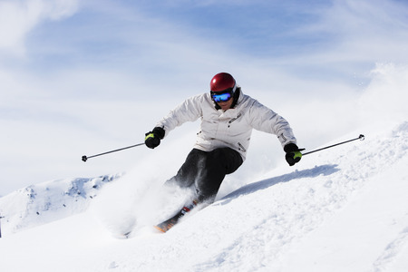 snows: Man in white with red helmet off-piste.