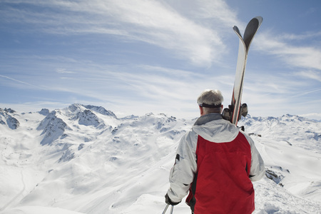 admired: Back view of mature man holding skis