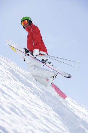 Man sin red carrying skis uphill.