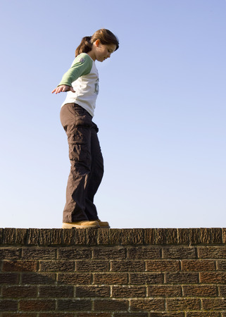 jeopardizing: Girl balancing on wall LANG_EVOIMAGES