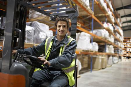 Worker on forklift, smiling to camera