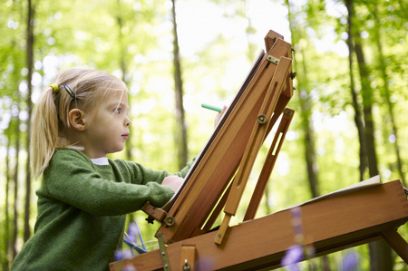 Girl painting in the forest LANG_EVOIMAGES