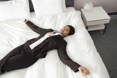 lay forward: Woman on a bed with arms outstretched